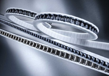 Transfer chains completely enclosed with wear-resistant Snap-On plastic attachments iwis